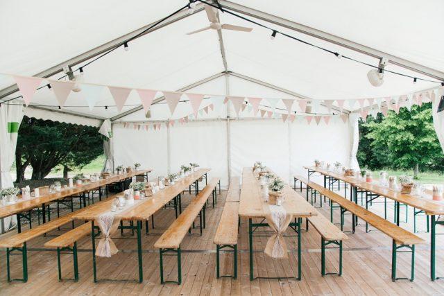 Tables de banquet sous une tente pour ce mariage champêtre organisé dans l'Ain - Photographe : Ksenia Vysotskaya