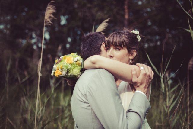 Photo de mariés dans les champs et bouquet de la mariée vert et jaune - Photographe : Adriana Salazar