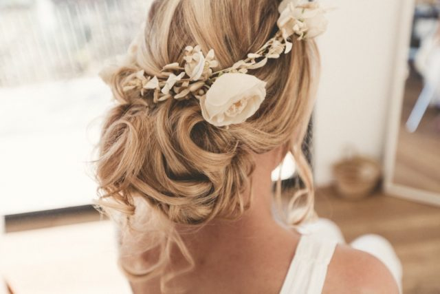 Couronne de fleurs blanche posée sur un chignon flou - Photographe : Adriana Salazar