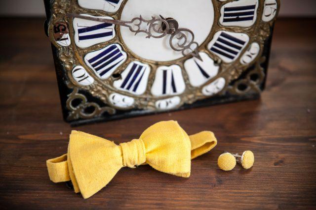 Le noeud papillon et les boutons de manchette du marié d'un mariage jaune et fleuri - Photographe : Eilean et Jules Photographie