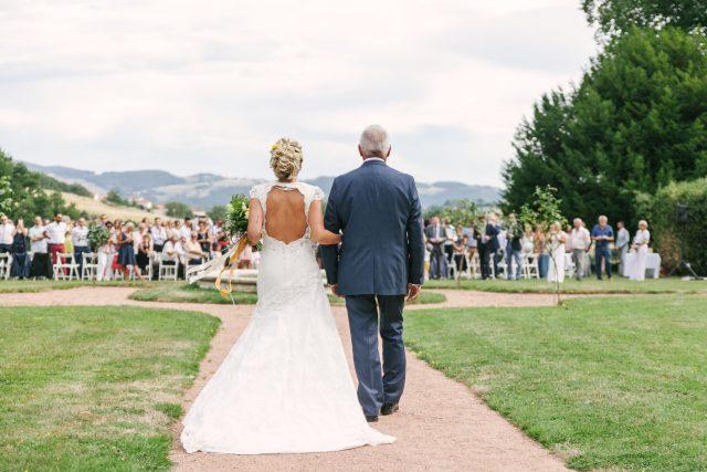 L'arrivée de la mariée à la cérémonie laïque d'un mariage jaune et fleuri - Photographe : Eilean et Jules Photographie